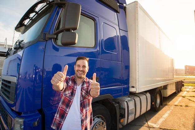 Portret van gelukkige glimlachende vrachtwagenchauffeur van middelbare leeftijd die zich door zijn vrachtwagen bevindt en duimen omhoog houdt.