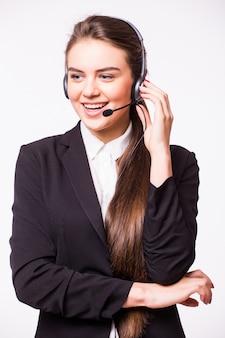 Portret van gelukkige glimlachende vrolijke mooie jonge telefoniste van de klantenondersteuningstelefoon in hoofdtelefoon, die over witte muur wordt geïsoleerd