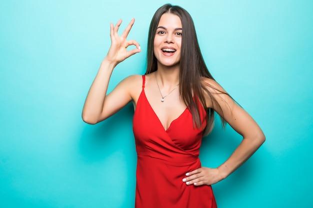 Portret van gelukkige glimlachende vrouw die rode kleding draagt die ok gebaar toont, duimen signaleert exemplaarruimte die op blauwe muur wordt geïsoleerd.