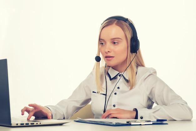 Portret van gelukkige glimlachende vrouwelijke telefoniste van de klantenondersteuning op de werkplek.