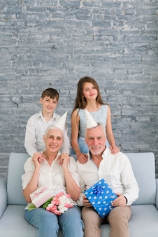 Portret van gelukkige grootouders dragen feestmuts met hun kleinkinderen
