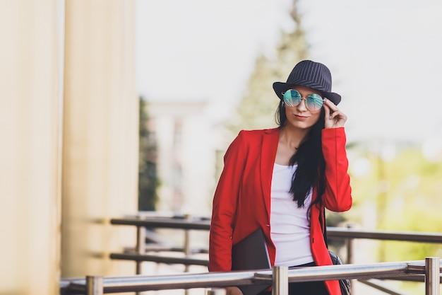 Portret van gelukkige hipster jonge vrouw met laptop die zonnebril, zwarte hoed en rood jasje draagt. studentenmeisje met laptop op universitaire campus