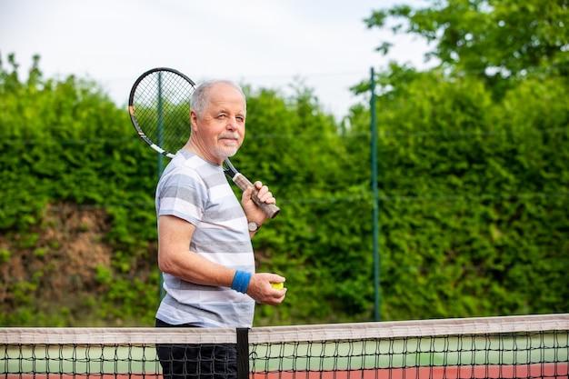 Portret van gelukkige hogere mens vóór zijn tenniswedstrijd, sportconcept