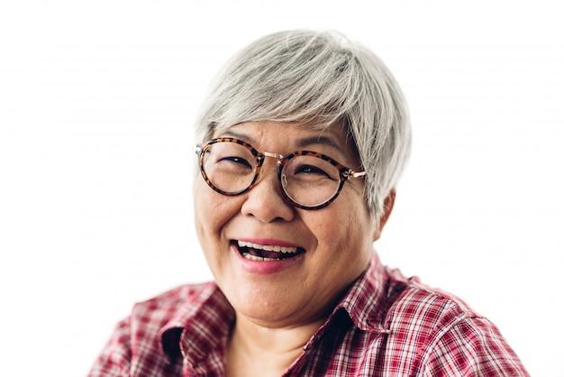 Portret van gelukkige hogere volwassen bejaarde aziatische vrouwen die op geïsoleerd wit glimlachen. het concept van de pensionering