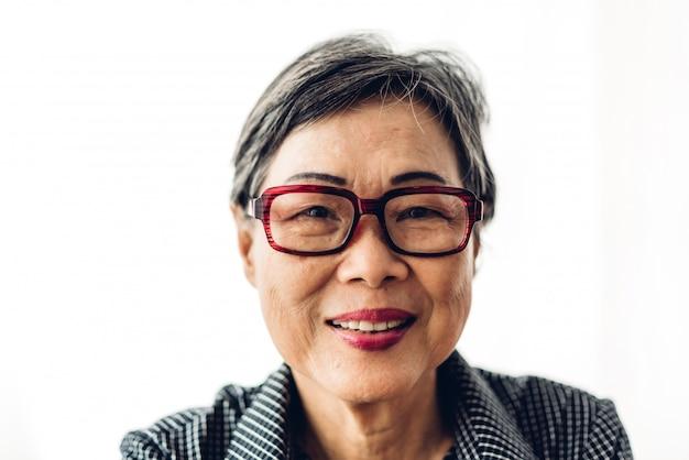 Portret van gelukkige hogere volwassen bejaarde vrouwen die van azië en camera op geïsoleerd wit glimlachen bekijken. het concept van de pensionering
