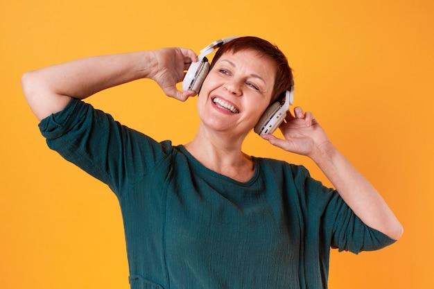 Portret van gelukkige hogere vrouw die aan muziek luistert