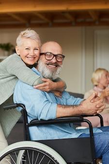 Portret van gelukkige hogere vrouw die haar gehandicapte echtgenoot omhelst en zij bij camera glimlachen