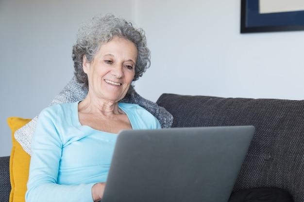 Portret van gelukkige hogere vrouw die laptop thuis met behulp van