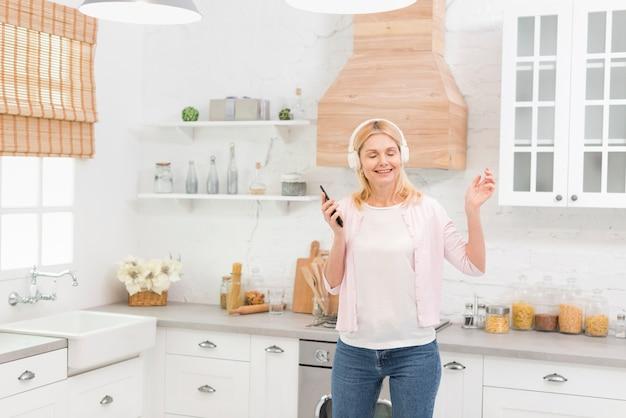 Portret van gelukkige hogere vrouw met hoofdtelefoons