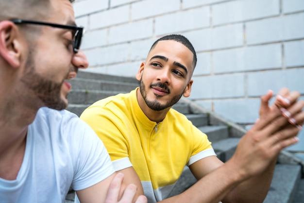 Portret van gelukkige homo paar tijd samen doorbrengen zittend op de trap buitenshuis. lgbt en liefde concept.