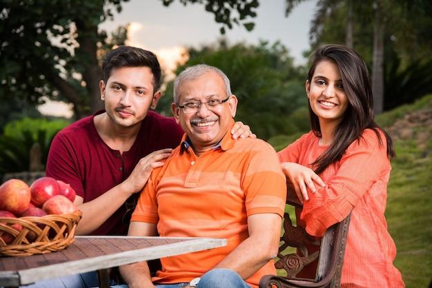 Portret van gelukkige indiase aziatische familie zittend op een tuinstoel, buiten