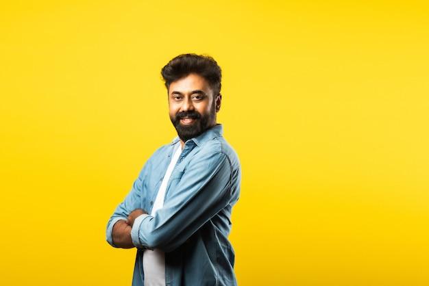 Portret van gelukkige indiase jonge bebaarde man met armen gekruist op geel on