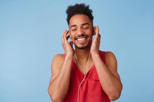 Portret van gelukkige jonge afro-amerikaanse man voelt geweldig, koptelefoon dragen, ogen sluiten en genieten van een nieuw album van favoriete band, geïsoleerd.
