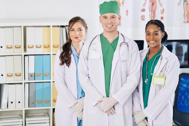 Portret van gelukkige jonge artsen die zich in medisch bureau bevinden en aan voorzijde glimlachen