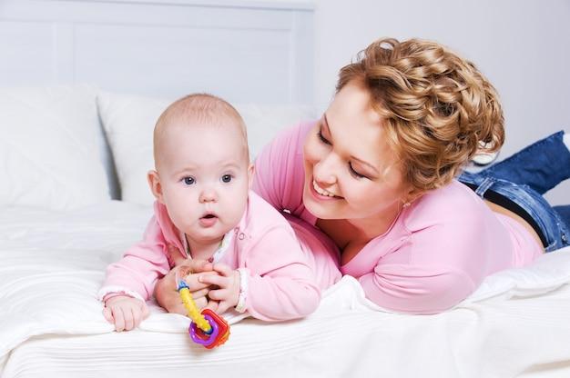 Portret van gelukkige jonge attactive moeder die met haar baby thuis op het bed ligt