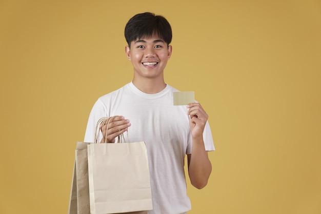 Portret van gelukkige jonge aziatische man gekleed terloops met boodschappentassen en creditcard geïsoleerd