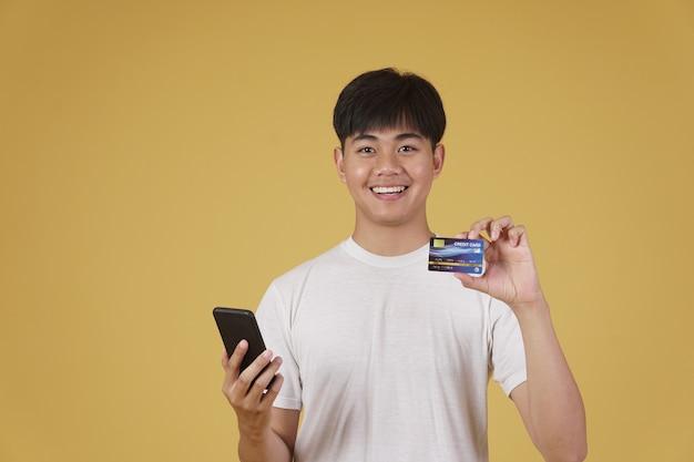 Portret van gelukkige jonge aziatische man gekleed terloops met smartphone en creditcard om online te winkelen geïsoleerd
