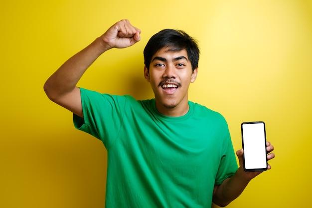 Portret van gelukkige jonge aziatische man in groen t-shirt wijzend op mobiele telefoon en kijkend naar camera met verbazing tegen gele achtergrond