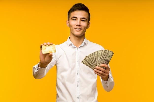 Portret van gelukkige jonge aziatische man met creditcard en geld in de hand glimlachend en camera kijken op geïsoleerde gele achtergrond positief voelen en genieten - beeld Premium Foto