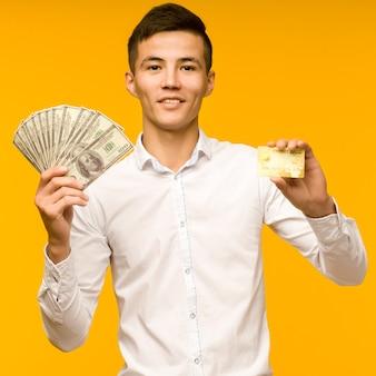 Portret van gelukkige jonge aziatische man met creditcard en geld in de hand glimlachend en camera kijken op geïsoleerde gele achtergrond positief voelen en genieten - beeld