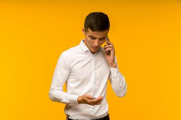 Portret van gelukkige jonge aziatische man met creditcard en praten aan de telefoon geïsoleerde gele ruimte