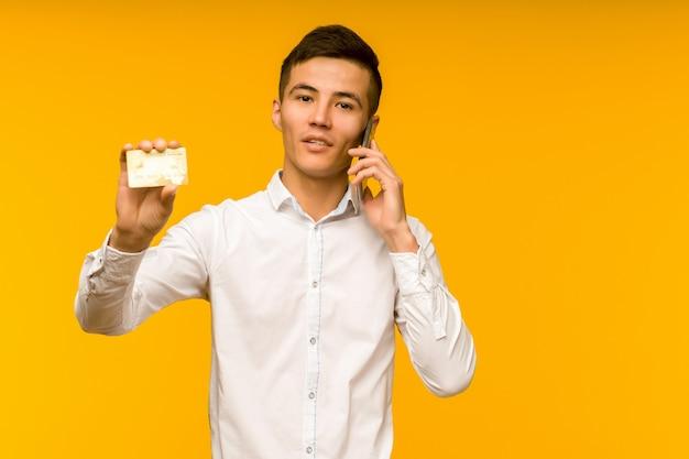 Portret van gelukkige jonge aziatische man met creditcard en praten aan de telefoon