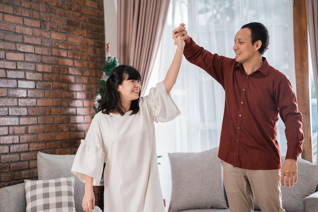 Portret van gelukkige jonge aziatische paar genieten van hun tijd samen door thuis in kerstdag te dansen