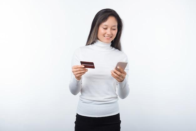 Portret van gelukkige jonge aziatische vrouw die creditcard en smartphone over witte achtergrond gebruiken