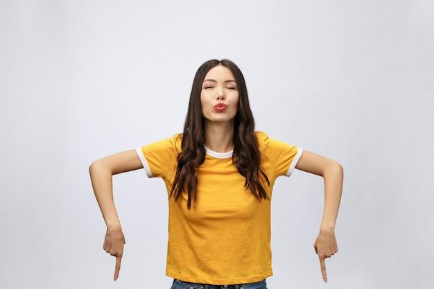 Portret van gelukkige jonge aziatische vrouw met vinger naar beneden wijzen