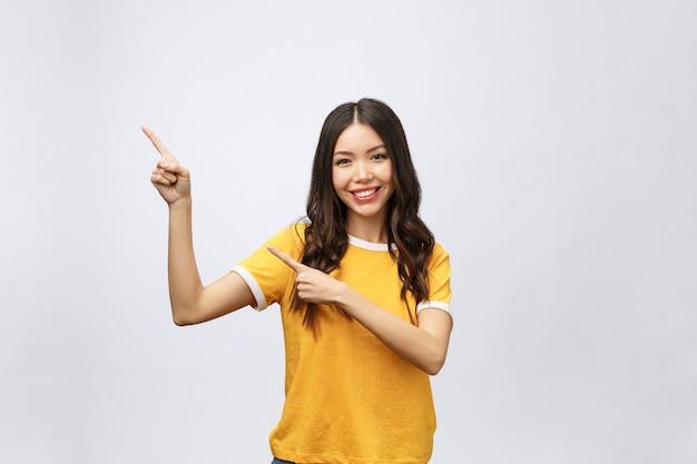 Portret van gelukkige jonge aziatische vrouw met vinger omhoog