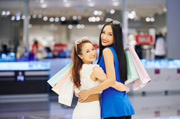 Portret van gelukkige jonge aziatische vrouwen die met boodschappentassen knuffelen die zich terugdraaien en naar voorzijde kijken