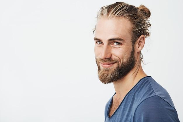 Portret van gelukkige jonge bebaarde man met modieuze kapsel en baard