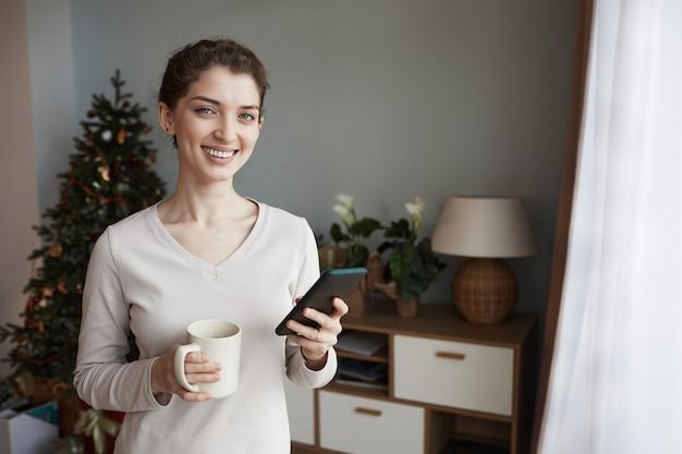 Portret van gelukkige jonge blanke vrouw in trui met mok in kamer met kerstboom en...