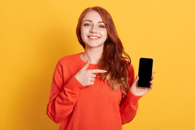 Portret van gelukkige jonge blanke vrouw wijzend op het lege scherm van de mobiele telefoon in haar hand geïsoleerd over gele ruimte