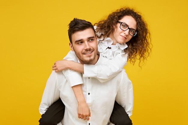 Portret van gelukkige jonge donkerbruine vrouw in oogglazen die van rit op de rug rit op de rug van vriendje tegen lege gele muur genieten. liefde, romantiek, saamhorigheid en geluk concept