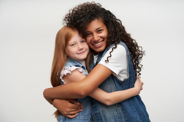 Portret van gelukkige jonge donkere vrouw met lang krullend haar vrij roodharige meisje knuffelen en breed glimlachen terwijl poseren op wit