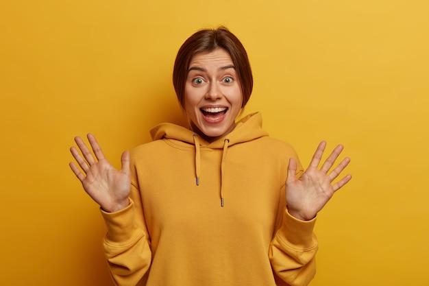 Portret van gelukkige jonge europese vrouw glimlacht positief, werpt handpalmen op en kijkt graag, verwacht niet zo leuk cadeau te krijgen, draagt casual gele hoodie in één toon met muur