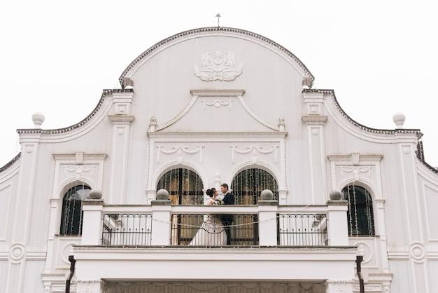 Portret van gelukkige jonge geliefden van de bruid en bruidegom op het balkon van een prachtig hotel. trouwdag