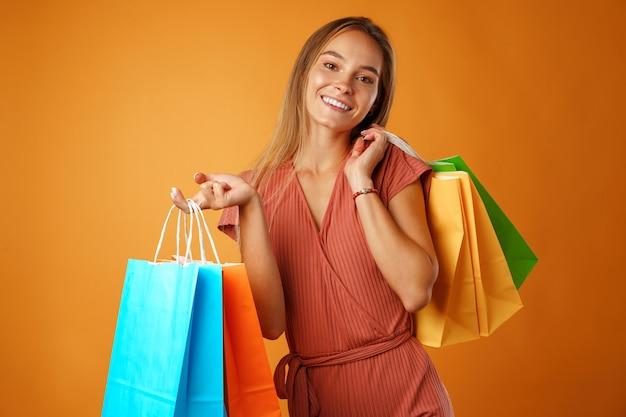 Portret van gelukkige jonge glimlachende vrouw met boodschappentassen