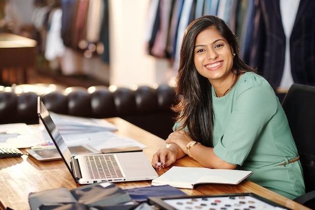 Portret van gelukkige jonge indische ateliereigenaar die aan laptop werkt