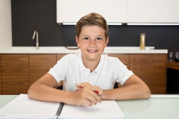 Portret van gelukkige jonge jongen die zijn huiswerk doet