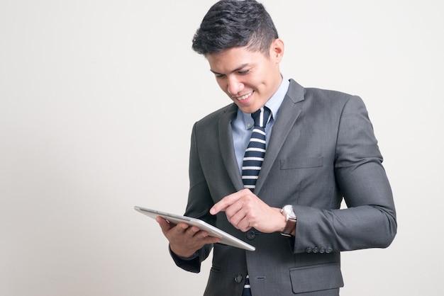 Portret van gelukkige jonge knappe aziatische zakenman die digitale tablet met behulp van
