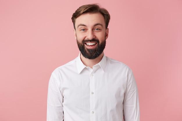 Portret van gelukkige jonge knappe bebaarde man, gekleed in een wit overhemd. wil een grappige grap vertellen. kijkend naar de camera en in grote lijnen lachend geïsoleerd op roze achtergrond.
