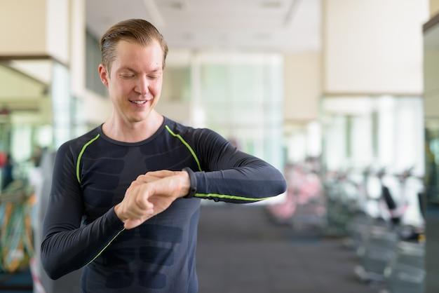 Portret van gelukkige jonge knappe man die smartwatch controleert in de sportschool tijdens covid-19