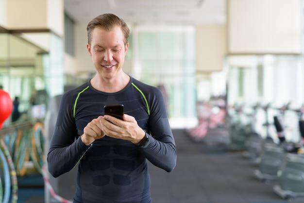 Portret van gelukkige jonge knappe man met behulp van telefoon in de sportschool tijdens covid-19