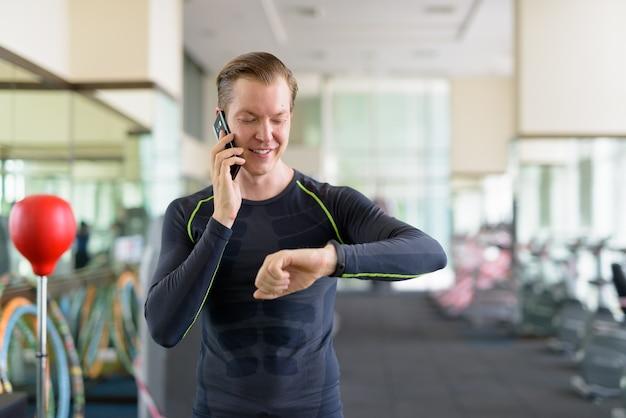 Portret van gelukkige jonge knappe man praten aan de telefoon en smartwatch controleren in de sportschool tijdens covid-19