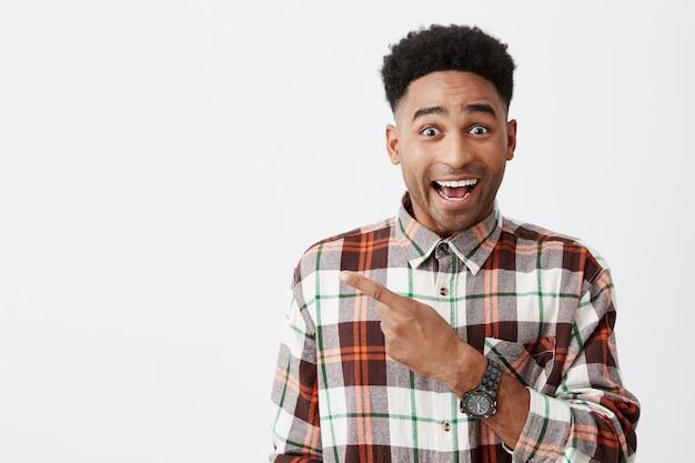 Portret van gelukkige jonge knappe tan-skinned mannelijke student met afro kapsel in casual geruit hemd glimlachen, opzij wijzen met vinger met opgewonden gezichtsuitdrukking