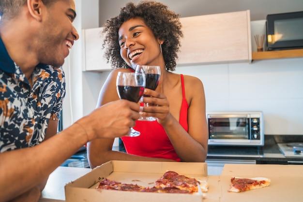 Portret van gelukkige jonge latijns-paar genieten van en eten bij nieuw huis. levensstijl en relatie concept.