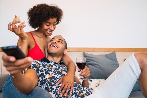 Portret van gelukkige jonge latijns-paar tijd samen doorbrengen en tv kijken in hun huis. levensstijl en relatie concept.