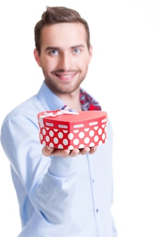 Portret van gelukkige jonge man met cadeau - geïsoleerd op wit.